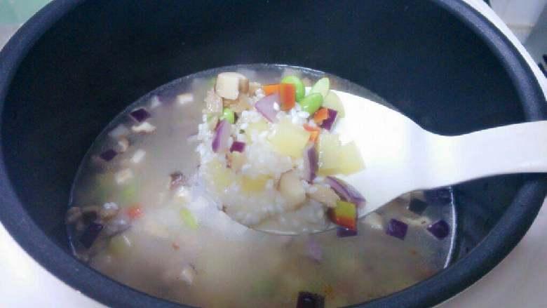 鸡肉彩蔬焖饭,将炒好的鸡肉蔬菜倒入米锅里,搅拌均匀。