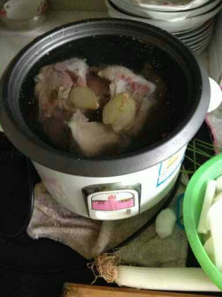 萝卜筒骨汤,电饭锅重新放水,放入姜蒜 片和筒骨,