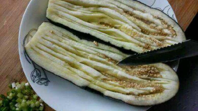 蒜蓉粉丝蒸茄子,蒸软后拿出来用刀划些口子。