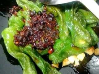 自创【虎皮青椒】,在放入炸好的青椒加适量豆瓣酱,放少许盐翻炒均匀。