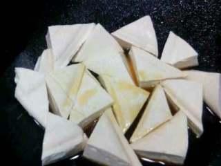 自创家常菜【豆腐烧木耳】,把切好的豆腐放进去炸。