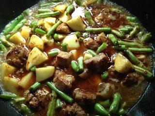 土豆四季豆烧排骨,放入土豆、四季豆,煮熟后放入盐、鸡精调味