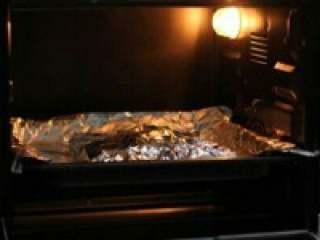 烤鱿鱼,6. 锡纸完全包裹鱿鱼(防烤糊)放 入预热好的烤箱中,上下火180度, 烘烤20分钟。