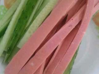自制简单版寿司,准备好的青瓜切成长条,火腿肠以切成长条。