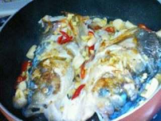 自制【鱼头豆腐火锅】,鱼头煎至好了,把姜,蒜,红尖 椒放入。