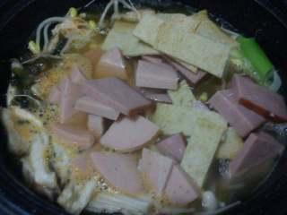 【韩式部队火锅】,金针菇变软后放入豆芽,切好的鱼饼和火腿。
