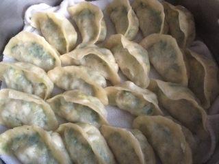 韭菜鸡蛋蒸饺,如图蒸锅添入足量的水,铺上蒸布,将饺子均匀的放在蒸布上