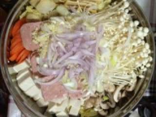 芝士年糕火锅,大蒜切成蒜末,洋葱切条状,大葱斜切圈状,平铺蔬菜上