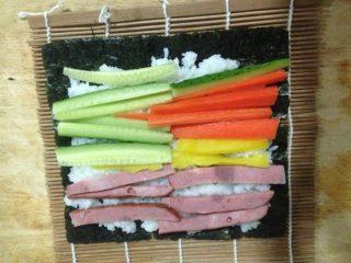 寿司,将切好的食材平铺在米饭上,如图