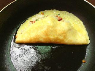 日式蛋包饭,如图再放入炒好的米饭将鸡蛋另一面翻过去