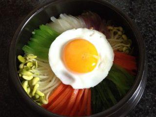 石锅拌饭,把蔬菜摆放在米饭上面,再放上鸡蛋,将石锅放火上加热至滋滋响,闻到焦香即可,撒点黑芝麻装饰
