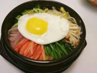 石锅拌饭,然后在蔬菜上放上煎好的太阳蛋。 将石锅放在火上加热,直至发出滋滋的声音,锅底米饭略焦即可。