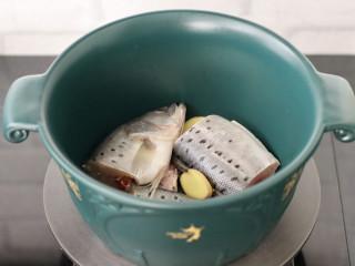 鲈鱼炖豆腐,另起砂锅,倒入少许油,放入姜片和切块的鲈鱼,小火慢慢煎至。