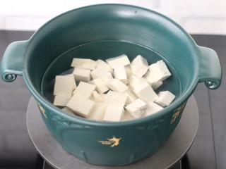 鲈鱼炖豆腐,砂锅里倒入适量清水,放入切小块的豆腐焯水捞出沥干水分,这样炖出来的豆腐豆香味浓郁嫩滑。
