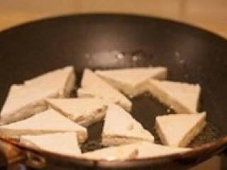 煎豆腐,煎锅中倒入少许油,待油温八成热时,将豆腐块放入,一面定型后把豆腐翻面,其间可轻轻晃动锅,以免豆腐巴锅