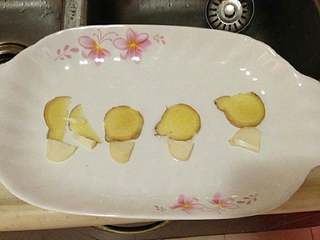 【清蒸大闸蟹】,盘子里先放上一些姜片和蒜片。