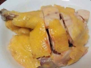 白切鸡,捞出放在案板上,摊凉后切件,装盘上桌