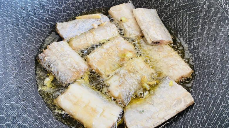 糖醋带鱼,锅中加入食用油加热至七成热,放入带鱼小火炸至两面金黄色