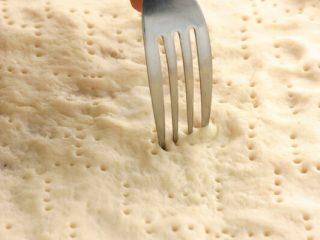 素食披萨,工作台上撒上少许高筋面粉,将作法6面团沾少许高筋面粉,用手压成圆饼状,用叉子在面皮戳小洞即可。