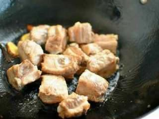 排骨焖饭,锅里放入少量橄榄油,放入姜片八角爆香后加入焯水后的排骨,放冰糖炒至表面微微发黄。