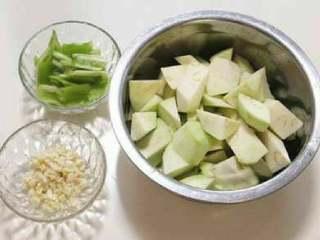 烧茄子,将茄子去皮切块、青辣椒切块、蒜切末备用,往茄子块中放一小勺盐拌匀,然后腌十分钟。