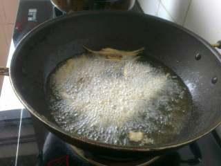 干炸多春鱼,锅内放油烧热,将每条腌渍好的多春鱼依次放入锅内;