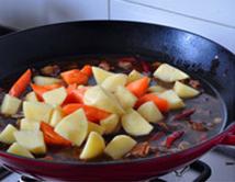 八宝豆豉焖羊肉,加入胡萝卜和土豆,继续焖炖至所有材料熟烂