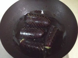 妈妈风味茄子,准备工作完成后就开始煎茄子了。油锅里的油放得要比平时炒菜多一些,油稍热就可以把茄子放进,先煎瓤那一面。