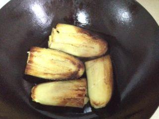 妈妈风味茄子,等闻到焦香味就可以翻面,煎背部。一边煎一边要用锅铲使劲按压,为了让油进入将茄子煎透,也为了让茄子水份全部出来。