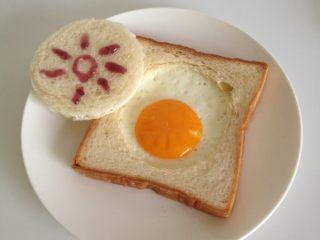 吐司太阳蛋,装入盘中,抠出来的圆片吐司也别浪费,抹点果酱吃吧