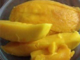 芒果班戟,如图: 将芒果去皮,沿果核切下果肉,再纵切成长条。