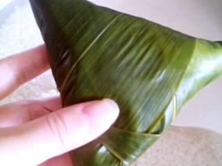 蜜枣粽子,然后再次加入米, 快满的的时候,灌入水,会自然流出后,粽子米会更紧实。按三角形卷起,如图。