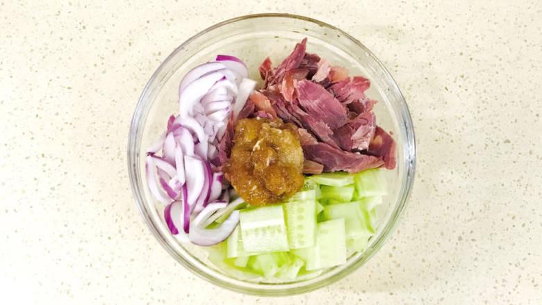 洋葱拌牛肉,将洋葱片、黄瓜片和牛肉加入搅拌碗中,加入大蒜泥