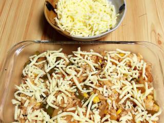 番茄海鲜饭,将炒饭放入烤盘中,大约烤盘高度一半的位置处,撒上一层芝士碎。