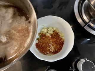 凉拌粉丝黄瓜,取耐热的碗,加入蒜末,葱末,小米辣,一汤匙辣椒粉,一汤匙熟白芝麻,分次浇上八成热热油,搅拌均匀