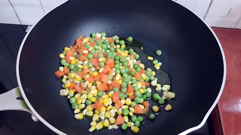 杂炒时蔬,倒入胡萝卜粒、豌豆、玉米粒翻炒片刻